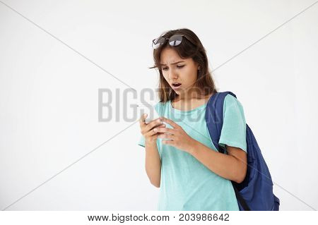 Modern technologies online communication people and human emotions. Picture of astonished mixed race female student with bag using smart phone having shocked look while receiving unexpected news