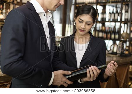 Woman Present Wine For Businessman At Bar. People With Business Concept.