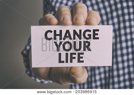 Change Your Life card in businessman`s hand