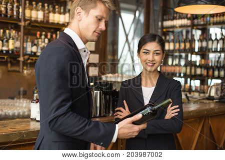 Woman Present Wine For Businessman At Bar With Attractive Smiling. People With Business Concept.