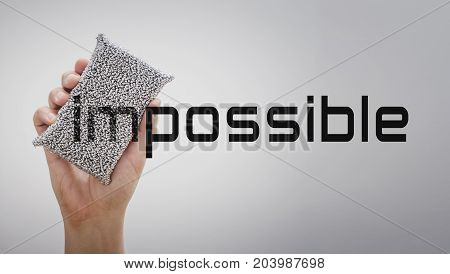 Hand erasing the word impossible to possible