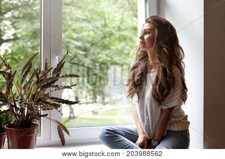 Pretty woman with long wavy hair relaxing by window in living room and looking through glass enjoying view outside. Joyful young female sitting on windowsill with plant pot feeling relaxed and happy