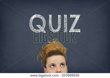Thinking woman with quiz word on blackboard background
