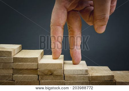 Hand climbing stairs made by wooden blocks. Business success concept.