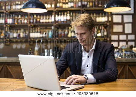 Man Using Laptop In Restaurant With Smiling, Man Working Concept