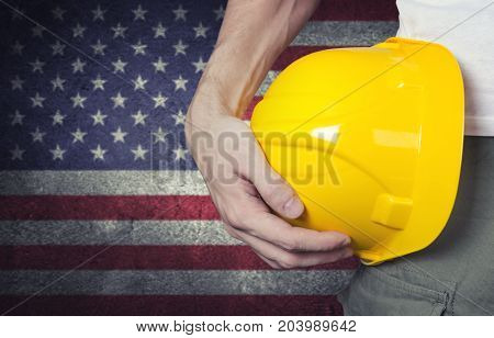 Worker with yellow helmet and USA national flag background. Labor day concept.