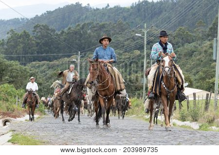 May 27 2017 Sangolqui Ecuador: young cowboy on horse back wearing chaps riding to a rural rodeo in the Andes