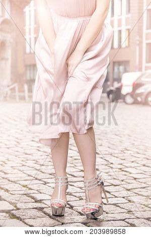 Crop woman wearing high heels and silk dress waving in wind holding skirt at street.