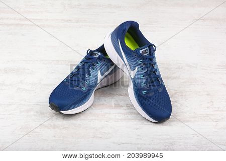 BURGAS, BULGARIA - SEPTEMBER 6, 2017: Nike Air Zoom Pegasus 34 Women's Running Shoes in blue on white wooden background. Nike is a global sports clothes and running shoes retailer.
