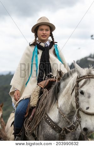 May 27 2017 Sangolqui Ecuador: female cowboy on horse back wearing poncho riding to a rural rodeo in the Andes