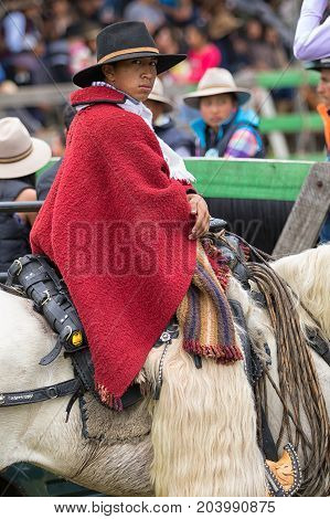 May 27 2017 Sangolqui Ecuador: young cowboy sitting in saddle wearing traditional wool poncho and furry chaps at a rural rodeo
