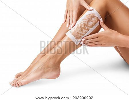 Female legs with epilating strips. Epilation procedure by waxing strips.