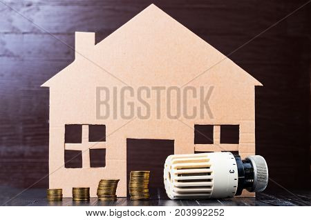 Home heat savings or expenses concept. Coin stacks radiator regulator house shape.