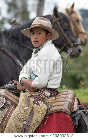 May 27 2017 Sangolqui Ecuador: young cowboy sitting in saddle wearing traditional furry chaps at a rural rodeo