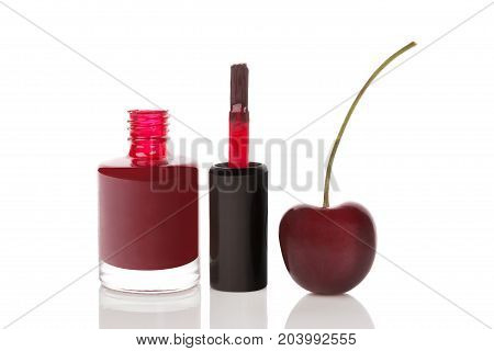 Glossy nail polish bottle with cherry isolated on white background.