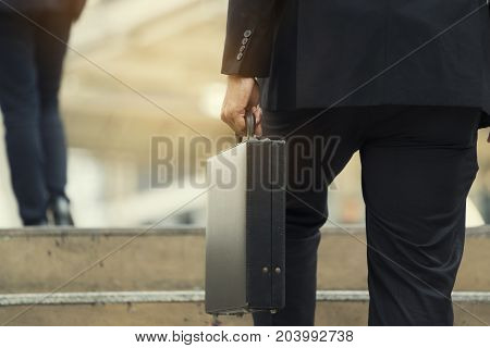 Businessman climbing up a concrete staircase concept on success