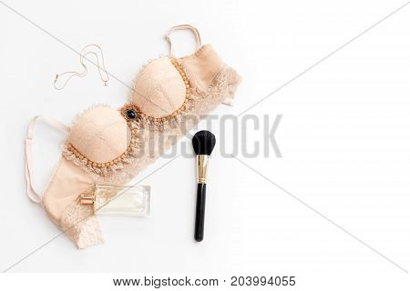 Glamorous stylish sexy lace lingerie with woman accessories on white background. Woman lace bra with perfume and necklace, flat lay, top view. Shopping and fashion concept, textile, jewelry, underwear