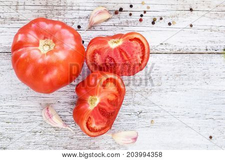 Top View Of Red Tomatos, Garlic And Pepper On White Wooden Background