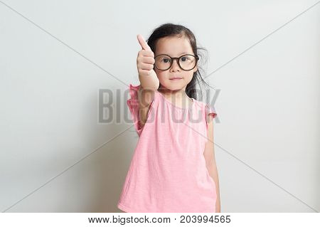 Little girl dressed in pink is showing thumb up gesture isolated over white background .