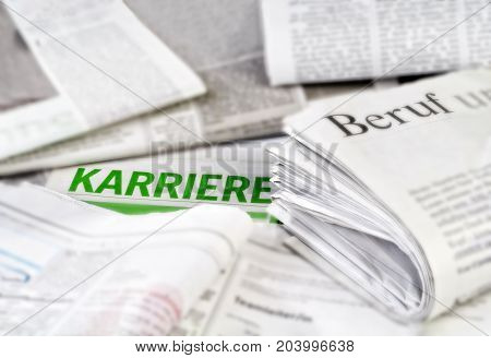 Various newspapers with several job advertisements and the german word for career