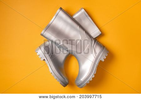 Autumn creative shot: stylish silver gumboots composed criss-cross on orange background. Top view. Flat lay.