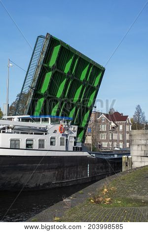 Green modern drawbridge with big boat under it in the day in Amsterdam