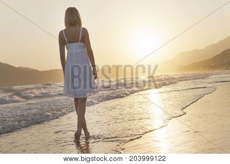 A girl is walking along island coastline at the sunset time. Chillout concept