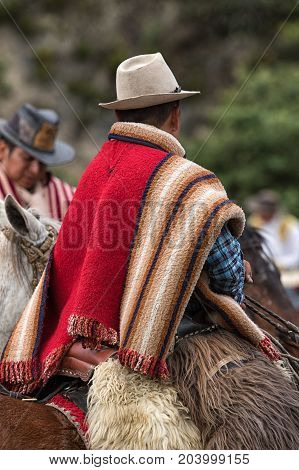 May 27 2017 Sangolqui Ecuador: cowboy from the high Andes wearing a traditional wool poncho at a rural amateur rodeo