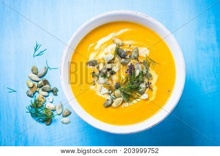 Pumpkin and carrot cream soup with seeds and herbs in the bowl on blue table. Top view. Traditional autumn food.