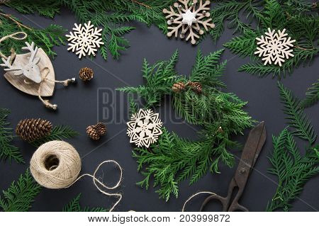 Preparation for Christmas holiday. Christmas workshop of wreath decor twine twigs and snowflakes. Top view and copy space. Flat lay. Workshop.