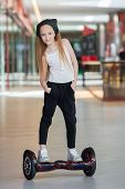 Happy and smiling girl rides on mini segway at trading mall. Teenager riding on hover board or gyroscooter poster
