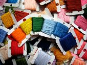 embroidery floss in rainbow colors on a flosses background. poster