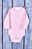 Baby girl striped long sleeve romper. Infant girl cotton bodysuit hanging on clothesline on grey wooden background. poster