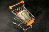 Chiniese leader Mao face in shopping cart with a paper banknote of One Chinese Yuan, as a symbol of the modern international economy poster