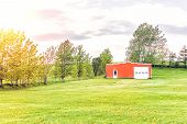 Landscape view of farm in Ile D'Orleans Quebec Canada with red painted vintage shed field dandelion flowers during sunset with sun sunlight golden warm sunrays poster