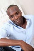 Handsome black man relaxing at home poster