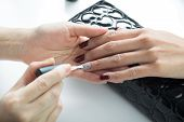 Manicure and pedicure series: Manicurist applying clear nail polish on customer's gel nail poster