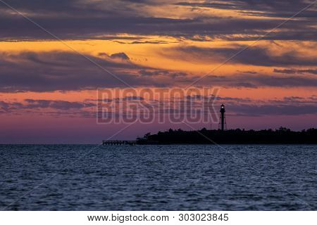 Gorgeous Colors Fill The Sky At Daybreak Silhouetting The Point Ybel Light, A Metal Lighthouse On Sa