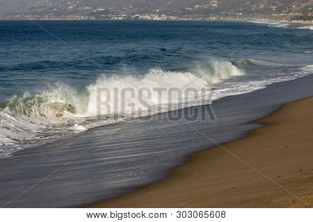 Breaking Wave With Backwash On Sandy Beach With Glow On Backwash And Sand