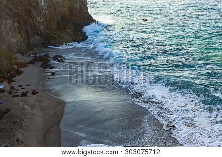Waves Breakaing With Foam On Sandy Beach With Backwash Against Cliff Wall
