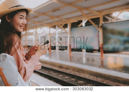 Woman Traveler With Backpack Use Mobile Smart Phone At Train Station. Trip Journey Travel Concept