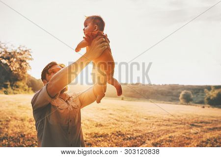 Father Holding Baby Up In The Air Playing Together Family Lifestyle Daddy And Child Walking Outdoor