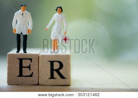Miniature People: Doctor And Nurse Standing On Wooden Block With Words Er. Health Care And Emergency