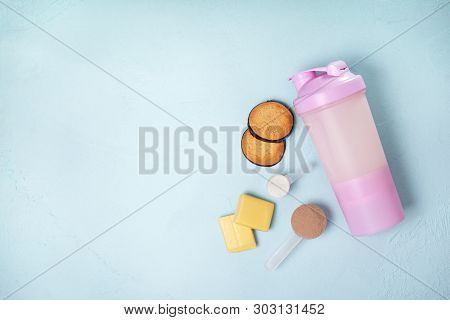 Shake With Protein Drink, Protein Powder, Protein Bars And Protein Cookies On A Blue Background. Vie