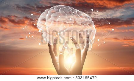 Mind And Mental Health. Female Hands Touching Brain With Network Connections, Sunset Sky Background