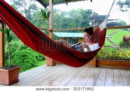 Bahia Drake Viallege, Costa Rica - August 29th of 2010: Young woman reading a book on a hammock on a rainny day in Fincas Maresia lodge, Bahia Drake, Corcovado National Park, Costa Rica