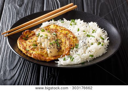 Portion Of Fried Chinese Omelet Egg Foo Young Served With A Side Dish Of White Rice Close-up On A Pl