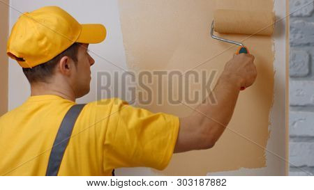 Young Worker Painting Wall Indoors. Handyman In Cap Painting The Wall With Paint Brush. Repair, Buil