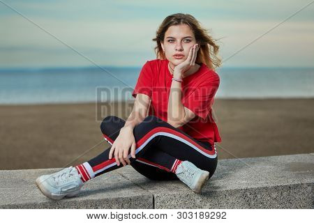 European Young Woman 20 Years Old With Blond Hair Is Sitting In Casual Wear On The Shore With Seriou