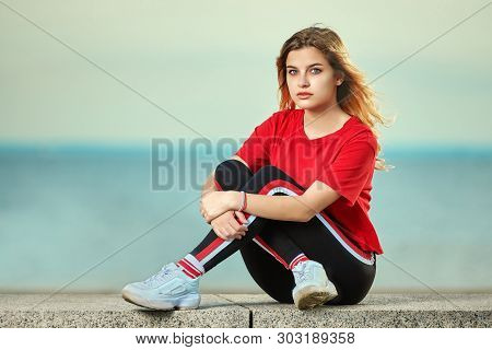 European Young Adult Woman18-20 Years Old Is Sitting On The Beach In Youth Clothes With Sea Shore On